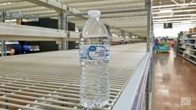 One bottle of water on an empty retail shelf