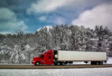 Reefer truck heading down highway with snow in the surrounding mountains and grass.