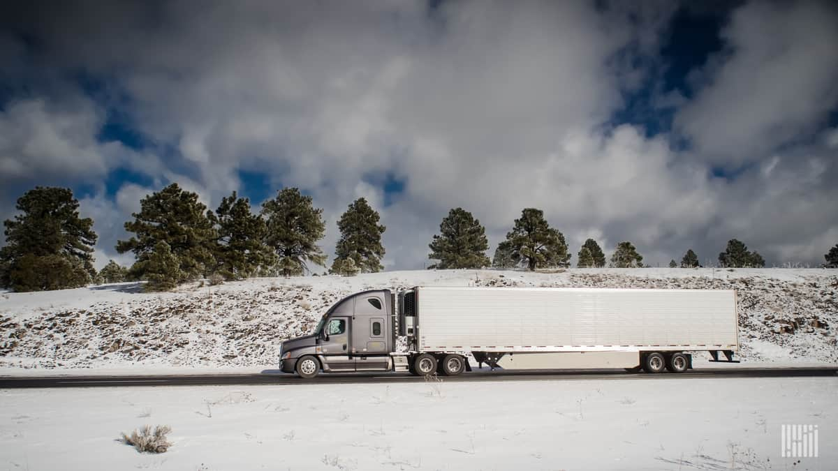 Reefer tractor-trailer heading down highway with snow-covered hills.