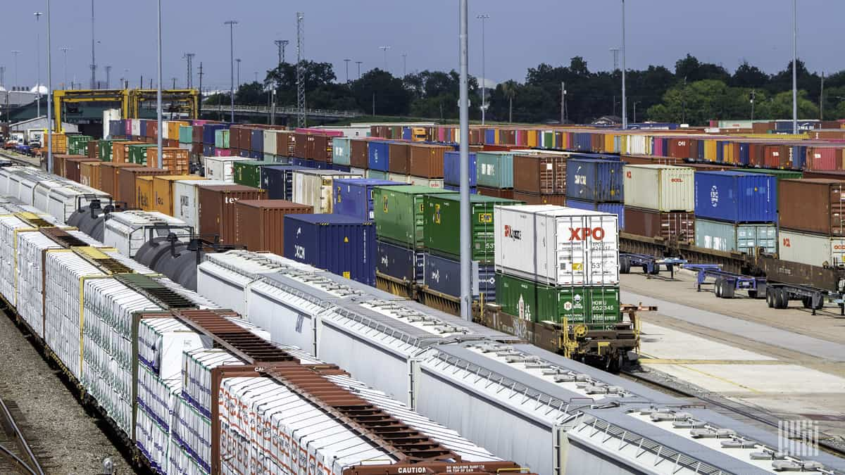 A photograph of intermodal containers and railcars parked in a rail yard.