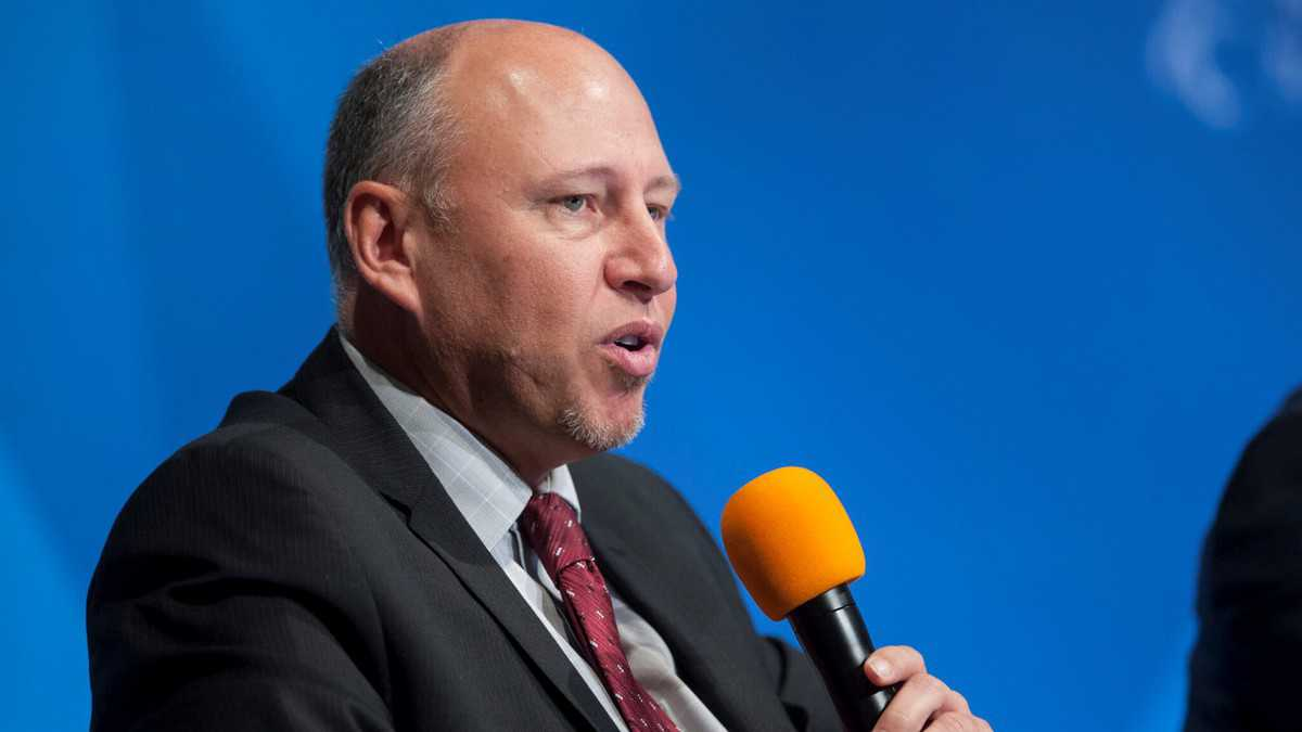 White man with receding hair speaking into handheld microphone at conference.
