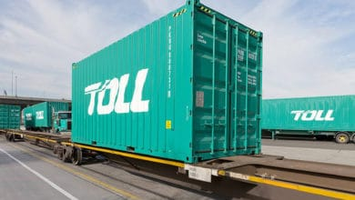 A green Toll Group container sitting on a rack.