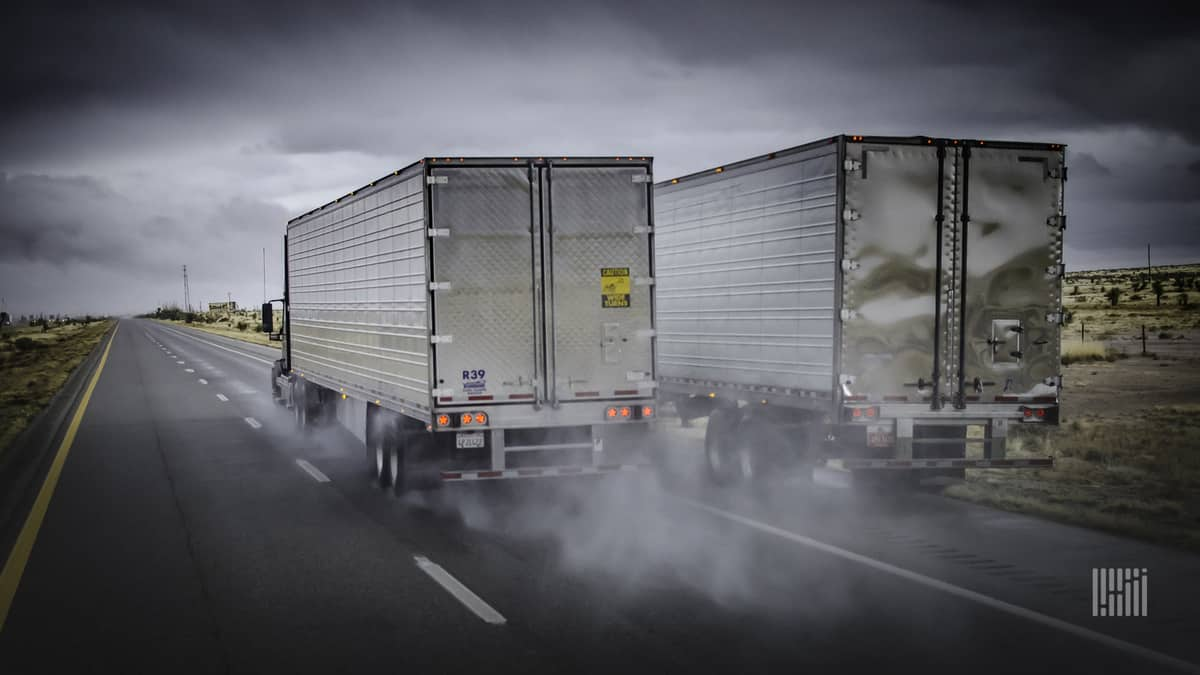 Two tractor-trailers, side-by-side, heading down a highway on a rainy day.