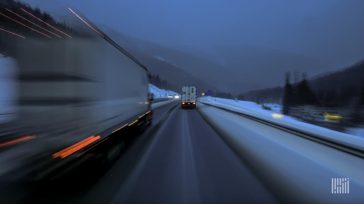 Tractor-trailers on a slick highway with snow on the side of the road.