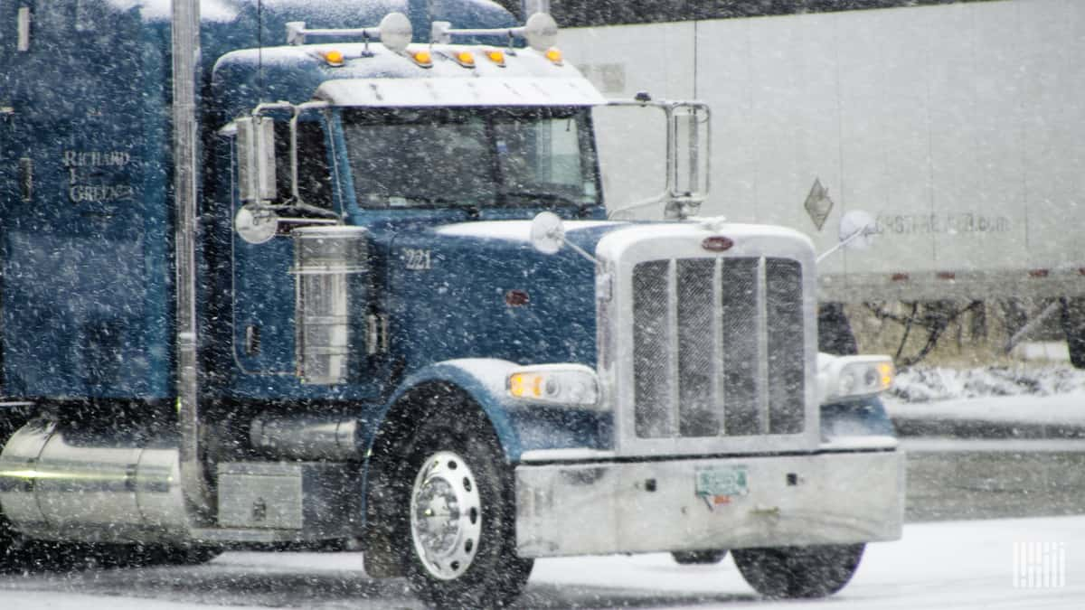 Tractor-trailer moving through blowing snow.