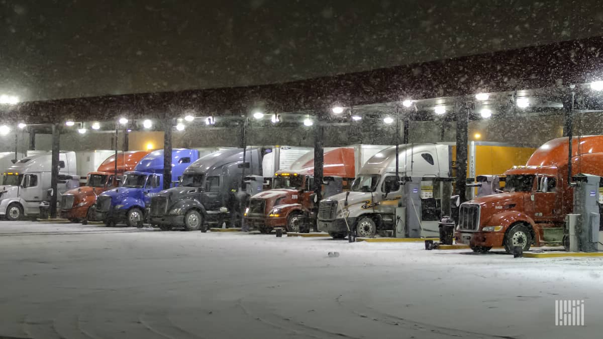 Tractor-trailers parked at a truck stop on a snowy night.