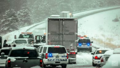 Tractor=trailers and cars in a traffic jam on a snowy highway.