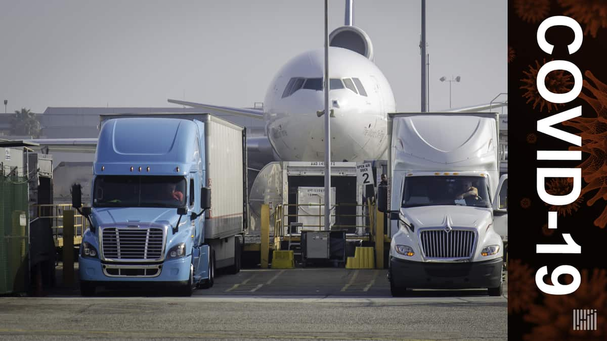 A big white jet flanked by a blue and white truck on each side of nose. COVID-19 banner since both types of transport will be used to deliver coronavirus vaccines.