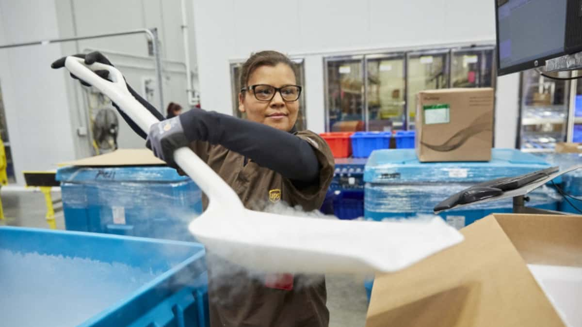 A UPS worker shovels dry ice into containers.