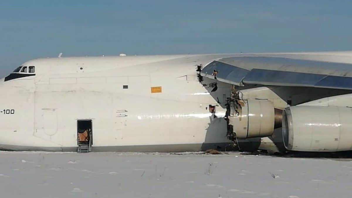 A big white freighter aircraft lies in snow at end of runway with damaged engine after emergency landing.