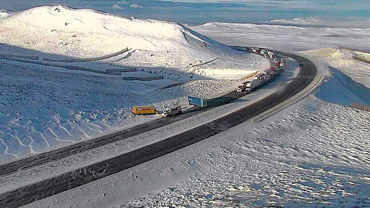 Tractor-trailers and cars on a snowy Wyoming highway.