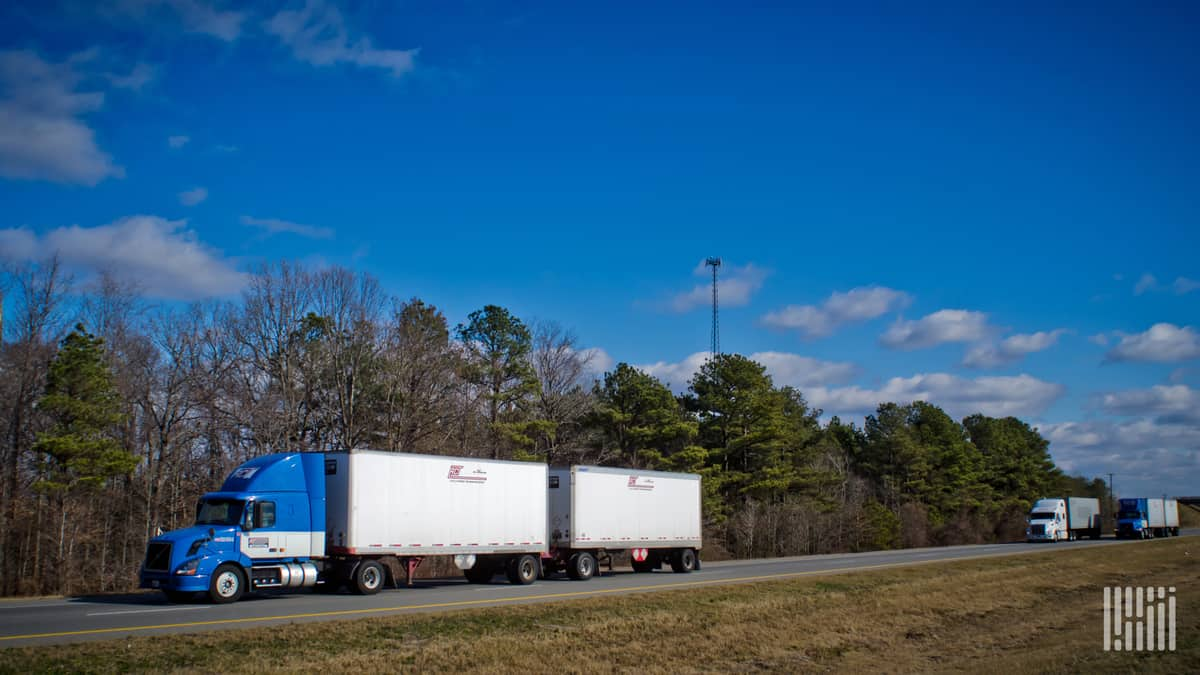 An AAA Cooper Transportation tractor hauls twin trailers down a highway. (Photo: Jim Allen/FreightWaves)