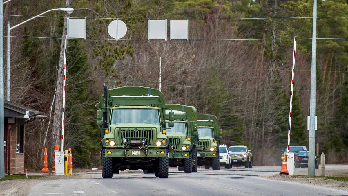 A convoy of military vehicles enters Canadian Forces Base Borden. The Canadian Armed Forces will be helping distribute COVID-19 vaccines.