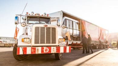 A semi-truck of Watson Transport with a trailer containing a rail car. QSL became full owner of Watson.