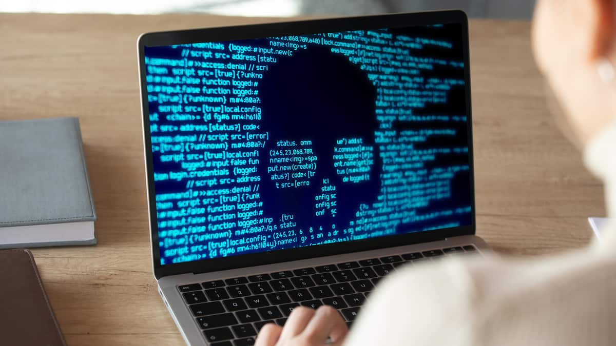 A laptop showing computer code and the outline of a skull to illustrate a ransomware attack.