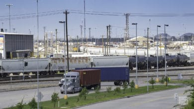 A photograph of a truck passing by a rail yard.
