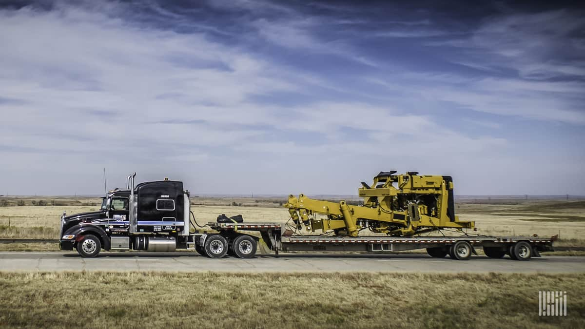 An ATS tractor hauls construction equipment on its flatbed trailer. (Photo: Jim Allen/FreightWaves)