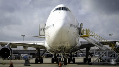 Front-end of a Boeing 747 cargo jet, looking straight on to its nose. The plane is white.