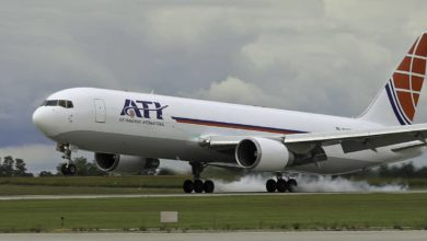 A large white plane with red tail touches down on runway. ATI is lettering.
