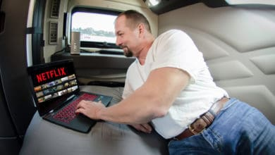 Truck driver in his sleeper selecting a streaming movie to watch.