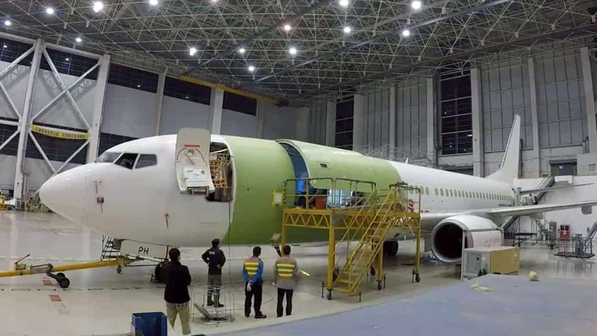 A Boeing 737 in a giant garage where it is being retrofitted with new equipment to carry cargo instead of passengers.