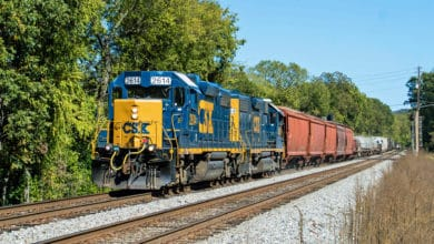 A photograph of a CSX train passing through a forest.