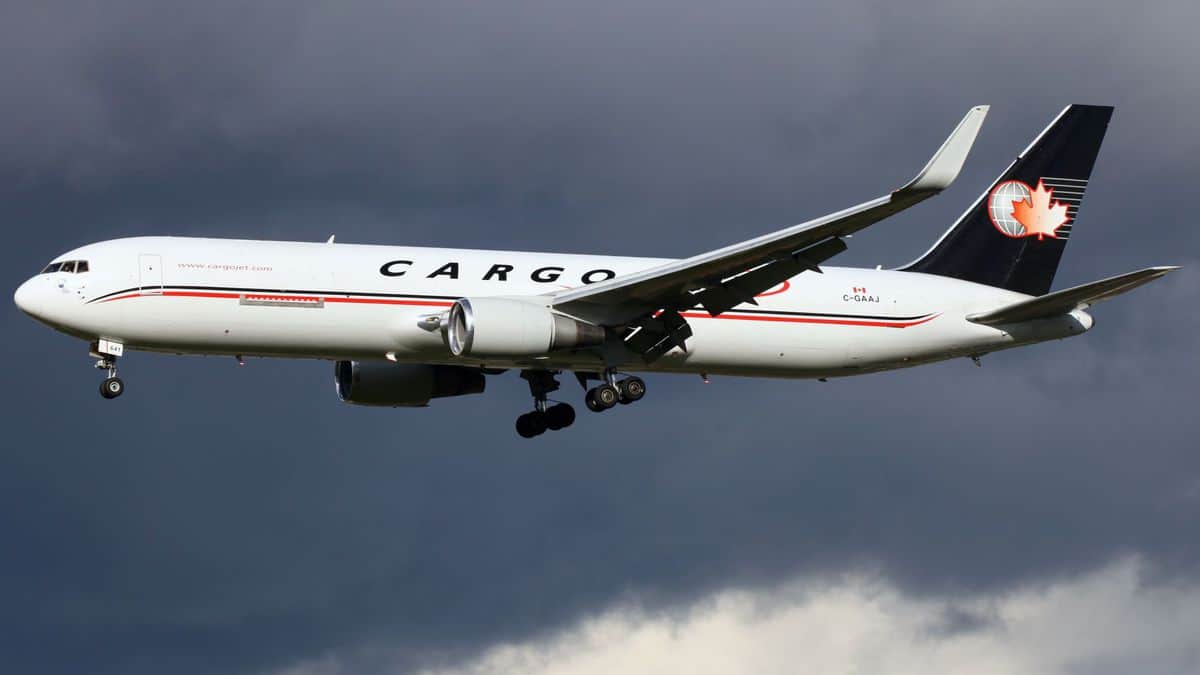 A white jet with a blue tail and the name Cargojet on its side has wheels down as it flies low to start landing.