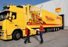 A bright yellow refrigerated DHL truck backed up to loading dock.