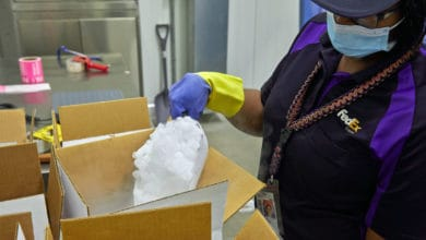 A FedEx employee packs a box with dry ice.
