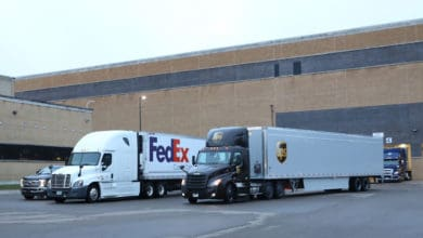 A FedEx and UPS tractor trailer at a loading dock.
