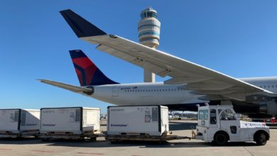 Temperature-controlled airfreight containers on carts being pulled to Delta plane for loading on sunny day. View of aircraft from below wing and towards back half of airplane.