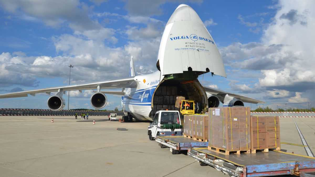 Huge cargo plane with its nose cone lifted so cargo dollies can be wheeled in.
