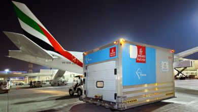 A cargo container on the tarmac at night after being unloaded from a large jet.