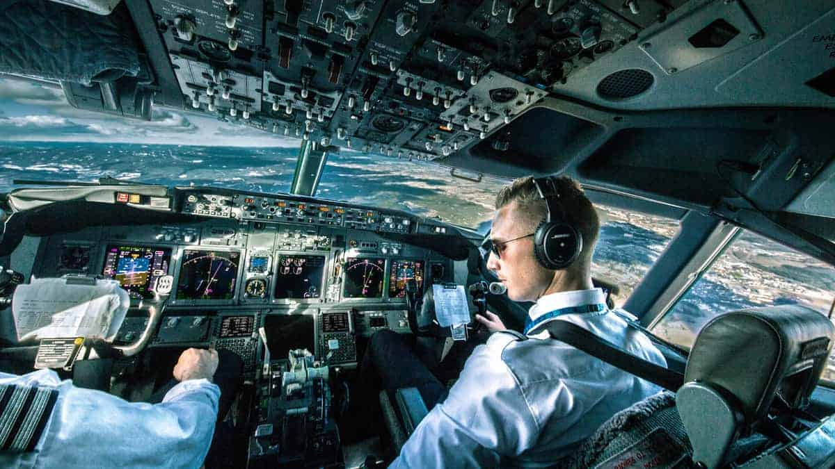 Pilots in cockpit looking out at sky, ground below..