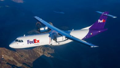 A white FedEx propeller plane flies on clear day, with ground visible below.