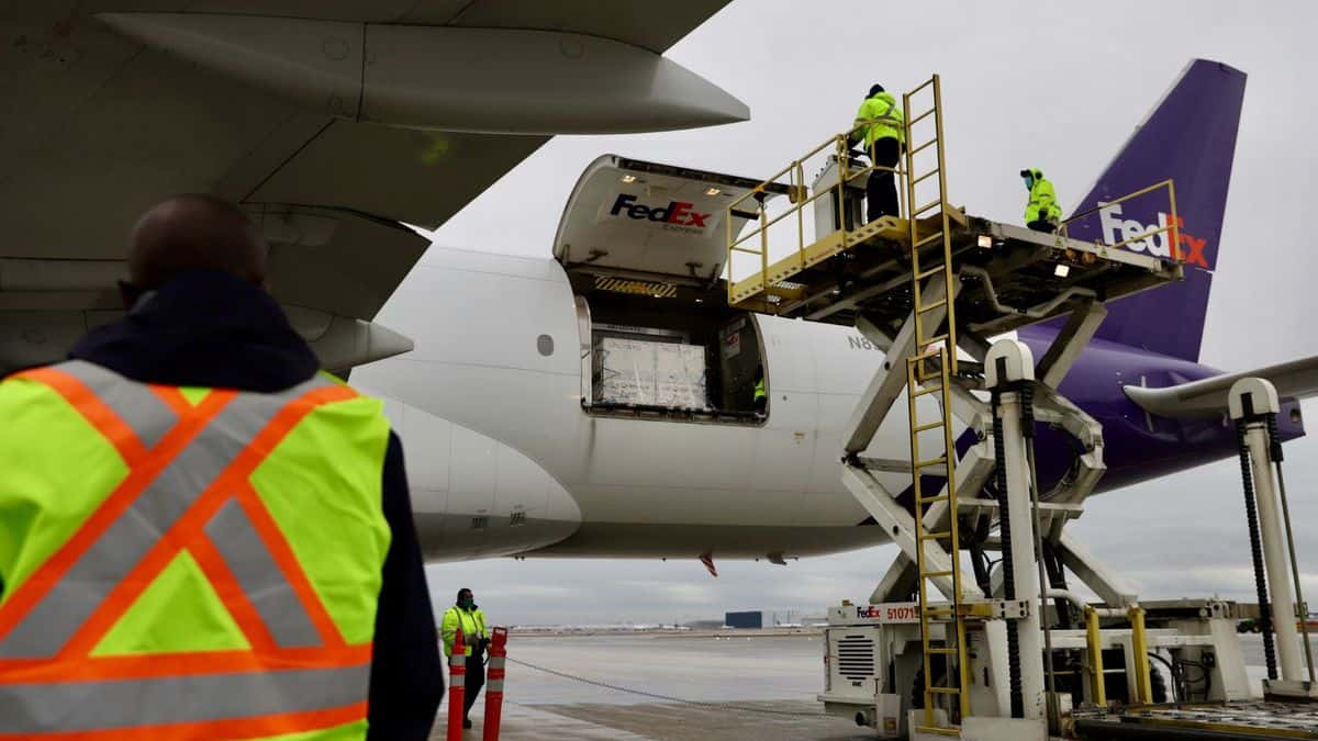 Hydraulic equipment lifts containers to rear door of a FedEx airplane.