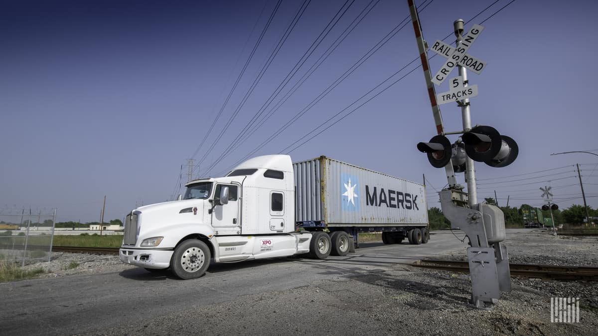 A photograph of a truck passing through a highway rail grade crossing.