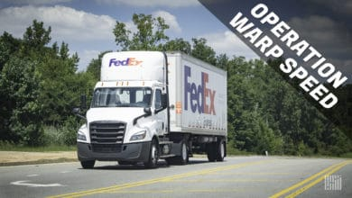 White FedEx truck driving on highway, headed towards us with Operation Warp Speed banner on side of photo for vaccine distribution effort.