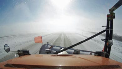 Plow truck heading down snowy Iowa road.