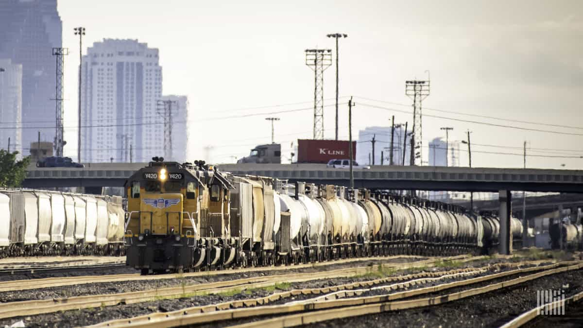 A photograph of a two trains sitting in a rail yard. Tall buildings are behind the rail yard.