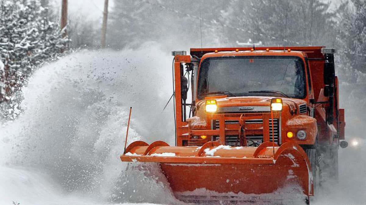 Plow truck clearing snow off a New Hampshire highway.