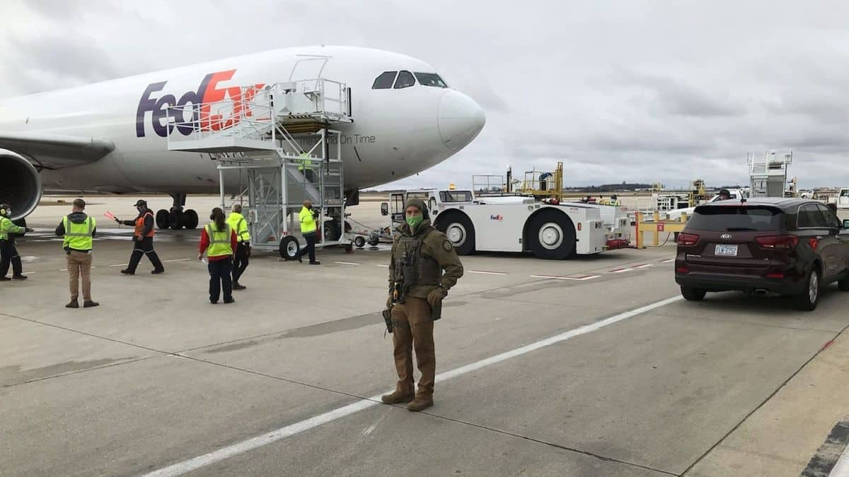 Armed guard on tarmac in front of a FedEx plane getting loaded with COVID vaccine.