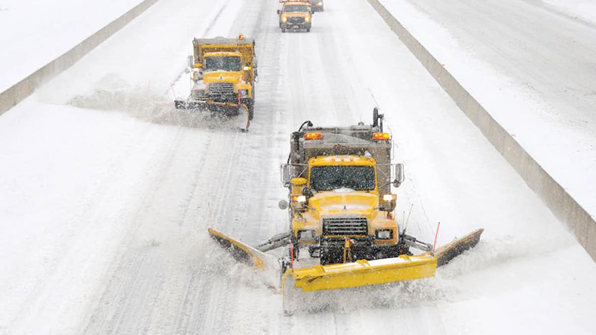 Plow trucks clearing a snowy Pennsylvania highway.