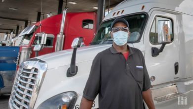 Black man wearing a face mask stands in front of white cab.