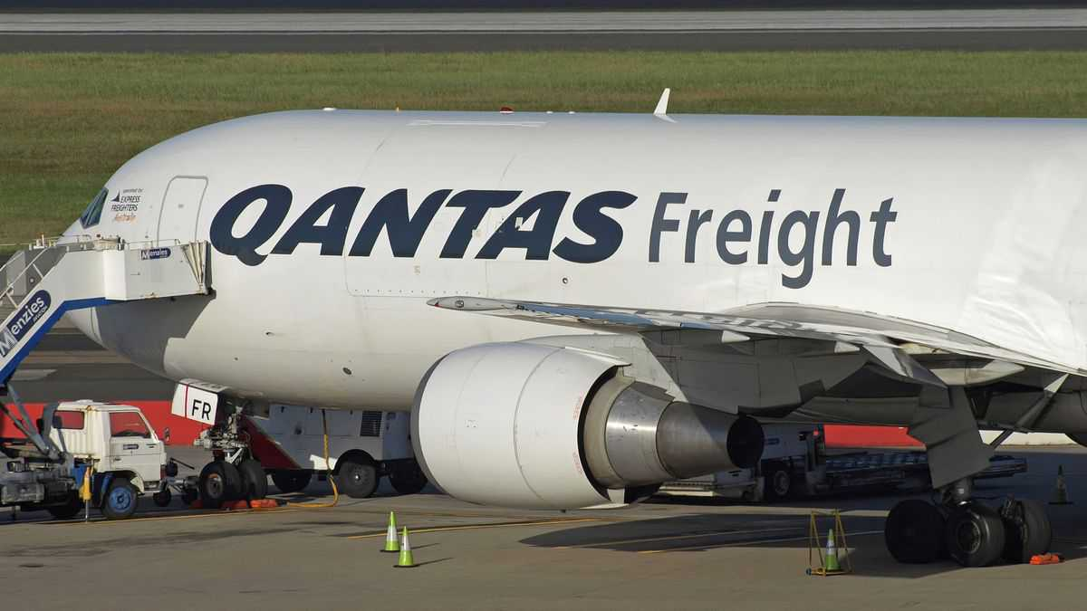A white Qantas Freight jet with black and red lettering parked at airport.