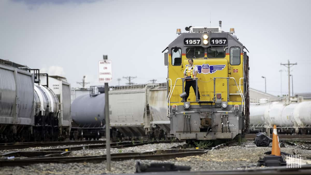 A photograph of a man stranding in front of a Union Pacific locomotive.