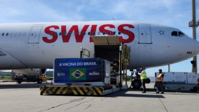 SWISS plane loaded with cargo on sunny day.