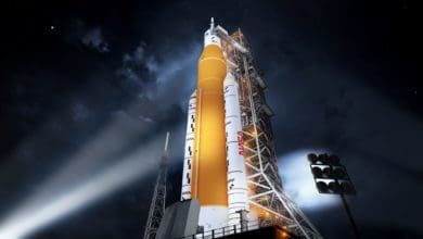 Artists image of flood light illuminating a giant rocket ship on launch pad at night.