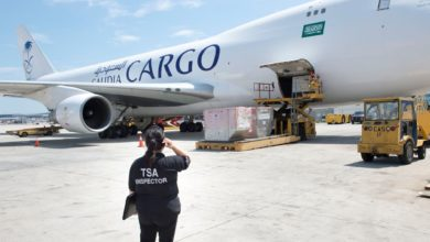 A TSA inspector watches a Saudia plane being loaded with pallets of cargo.