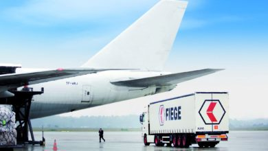 A white truck below tail of a white aircraft delivering cargo.